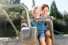 使用在冒险操场的两个男孩挖掘者在公园 免版税库存图片