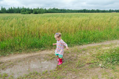 使用在农厂土的白肤金发的卷曲学龄前儿童女孩 免版税图库摄影