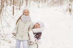使用在冬天森林里的两个女朋友 免版税库存照片