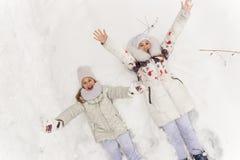 使用在冬天森林里的两个女朋友 库存照片