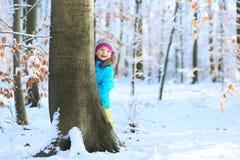 使用在冬天森林里的小女孩 免版税库存照片