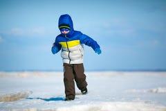 使用在冬天海滩的逗人喜爱的小男孩 库存图片