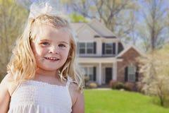 使用在前院的可爱的微笑的女孩 免版税库存图片