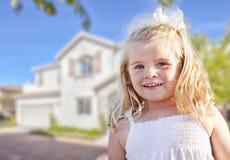 使用在前院的逗人喜爱的微笑的女孩 免版税库存图片