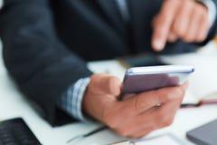 使用在办公室内部的巧妙的电话顶视图射击了人在衣服的` s手,使用手机的商人手在 免版税库存照片