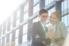 使用在办公楼之外的愉快的女实业家巧妙的电话在晴天 免版税库存图片