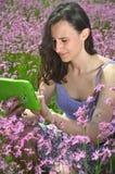 使用在华美的草甸的美丽的可爱的深色的女孩片剂 库存照片