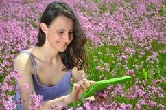 使用在华美的草甸的美丽的可爱的深色的女孩片剂 免版税库存图片