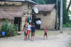 使用在原始的Tanu家庭,尼泊尔的村庄的孩子在chitwan的 免版税库存图片