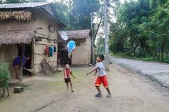 使用在原始的Tanu家庭,尼泊尔的村庄的孩子在chitwan的 库存图片