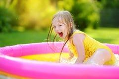 使用在可膨胀的婴孩水池的可爱的小女孩 飞溅在五颜六色的庭院戏剧中心的愉快的孩子在热的夏日 免版税图库摄影