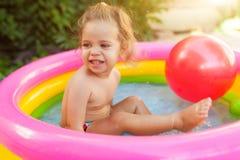 使用在可膨胀的婴孩水池的孩子 孩子在五颜六色的圆的水池游泳并且飞溅 库存图片