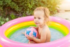 使用在可膨胀的婴孩水池的孩子 孩子在五颜六色的圆的水池游泳并且飞溅 免版税图库摄影