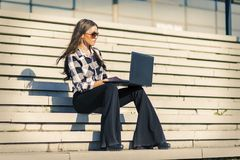 使用在台阶的可爱的妇女膝上型计算机室外 库存照片