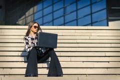 使用在台阶的可爱的妇女膝上型计算机室外 免版税库存图片