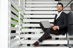 使用在台阶的年轻人一台膝上型计算机 免版税库存照片
