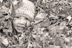 使用在叶子的愉快的小男孩 免版税库存照片