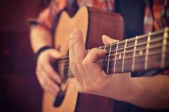 使用在吉他的吉他弹奏者 免版税库存图片
