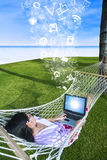 使用在吊床的亚裔妇女膝上型计算机在海滩 免版税库存照片