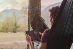 使用在吊床的年轻人一种片剂 图库摄影