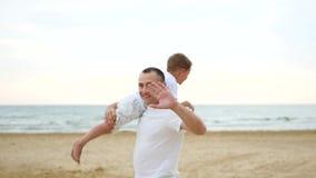 使用在含沙海滨的父亲和儿子 人运载他的肩膀的一个愉快,笑的男孩,挥动他的胳膊 股票视频