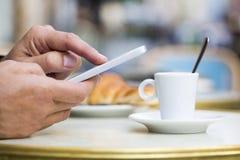 使用在咖啡馆大阳台、新月形面包和咖啡的人一个手机 免版税库存图片