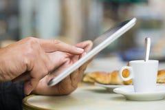 使用在咖啡馆大阳台、新月形面包和咖啡的人一台片剂个人计算机 免版税图库摄影