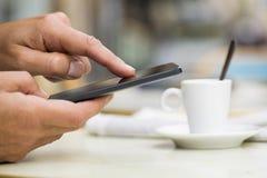 使用在咖啡馆大阳台、新闻纸和咖啡的人一个手机 库存照片