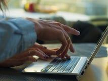 使用在咖啡馆的计算机妇女` s递键入在businessmans内部,侧视图的膝上型计算机键盘  库存照片