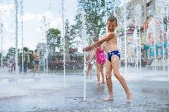 使用在喷泉和享用水的凉快的小河快乐的孩子在一夏天热的天 库存图片