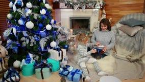 使用在圣诞树、母亲和女儿舒适大气的在房子里,趣味游戏附近的愉快的家庭与 股票录像