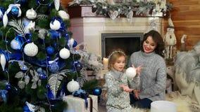 使用在圣诞树附近的母亲和女儿,在舒适大气的愉快的家庭在房子里,趣味游戏与 影视素材