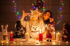 使用在圣诞节的愉快的女性朋友装饰了内部 免版税库存图片