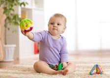 使用在地板上的一个地毯的婴孩gitl在托儿所 库存图片