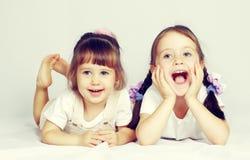 使用在地板上的两个可爱的小女孩 免版税库存照片