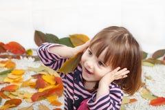 使用在地板上的女孩盖用秋叶 免版税图库摄影