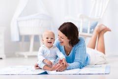 使用在地板上的母亲和婴孩 图库摄影