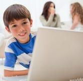 使用在地毯的男孩膝上型计算机有他的在他之后的系列的 库存照片