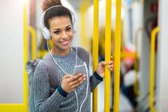 使用在地铁的少妇手机 免版税库存图片