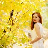使用在城市公园的秋天女孩。 秋天愉快的l妇女纵向  免版税图库摄影