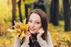 使用在城市公园的秋天女孩 秋天愉快的可爱和美丽的少妇妇女画象在秋天颜色的森林里 免版税库存照片
