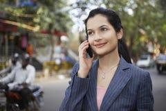 使用在城市街道上的女实业家手机 免版税库存照片