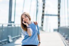 使用在城市街道上的美丽的愉快的年轻女实业家手机 库存照片