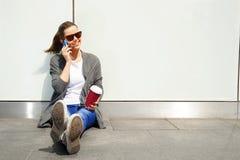 使用在墙壁的年轻愉快的青少年的女孩一个巧妙的电话在backg 免版税库存照片