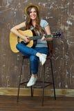 使用在声学吉他的微笑的少妇 免版税库存照片