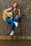 使用在声学吉他的微笑的少妇 免版税库存图片