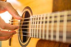 使用在声学吉他的人手 特写镜头 免版税库存图片
