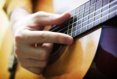 使用在声学吉他的人手 免版税库存照片