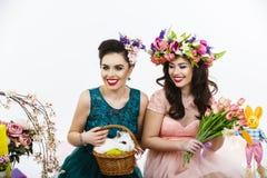 使用在复活节装饰的两名美丽的妇女用兔子 库存图片