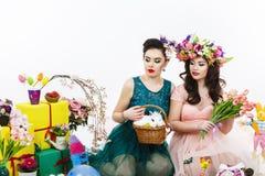 使用在复活节装饰的两名美丽的妇女用兔子 图库摄影